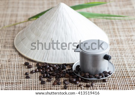 Vietnamese coffee brewing pot with coffee beans and conical hat