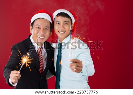 Vietnamese colleagues with Bengal lights hugging and looking at the camera - stock photo
