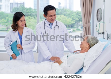 Vietnamese doctor and nurse talking to senior patient in ward - stock photo
