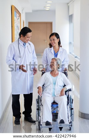 Vietnamese doctor and nurse walking with patient in wheelchair - stock photo