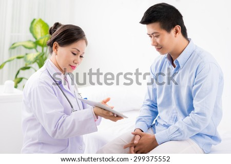 Vietnamese female doctor showing results of medical examination to the patient - stock photo