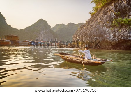 Vietnamese female in traditional boat returns to floating fishing village in the Halong Bay at evening. The Gulf of Tonkin, the South China Sea, Vietnam. Karst towers-isles are visible in background. - stock photo