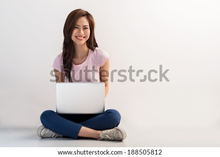 Vietnamese female sitting on the floor and working on the laptop