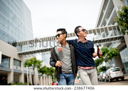 Vietnamese friends walking along the street and drinking beer - stock photo