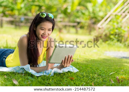Vietnamese girl lying on the grass and using digital tablet - stock photo