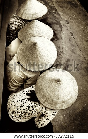 Vietnamese ladies sitting in a row showing their beautiful hats - stock photo