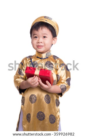 Vietnamese little boy in traditional Aodai, holding a red gift standing isolated on white background