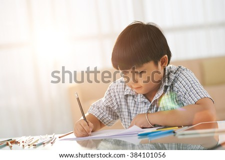 Vietnamese little boy sitting at table and drawing pictures