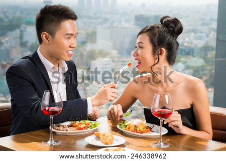 Vietnamese man feeding his gorgeous girlfriend while both relaxing in the luxurious restaurant