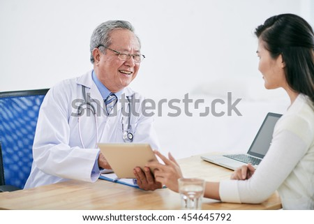 Vietnamese mature doctor with tablet computer talking to patient