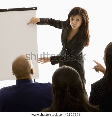 Vietnamese mid-adult woman standing in front of business group pointing to presentation.