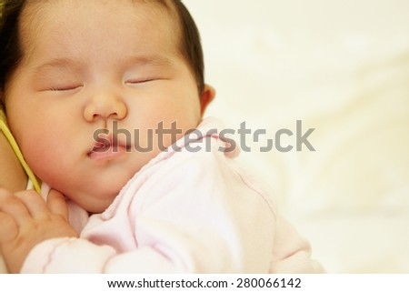 Vietnamese mother cuddling baby - stock photo
