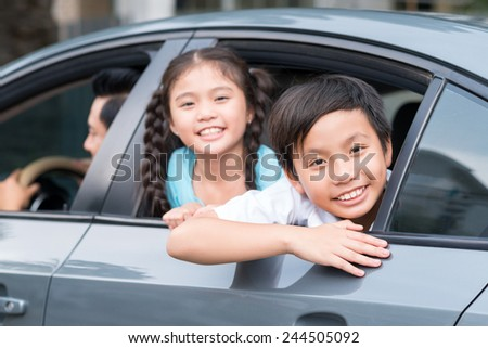 Vietnamese sibling looking out of the car window - stock photo