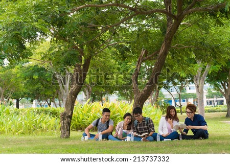Vietnamese students sitting in the park and studying together - stock photo
