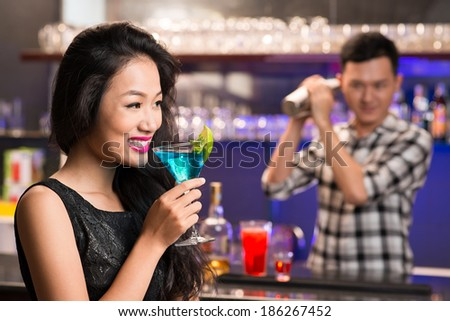 Vietnamese woman drinking a cocktail in the bar