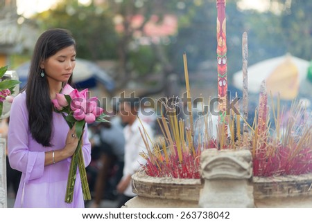 Vietnamese woman praying at temple holding lotus flower buds bunch - stock photo