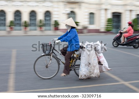 Vietnamese woman riding her bicycle with an iconic conical hat through Ho Chi Minh City. Note panning shot with motion blur. - stock photo