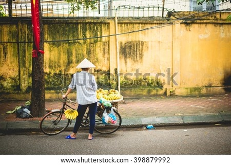 Vietnamese woman with her bike, selling goods at the street