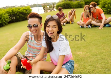 Vietnamese young couple sitting on the grass and drinking beer at the party - stock photo