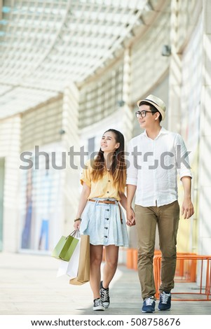 Vietnamese young couple walking in shopping mall