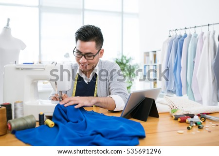 Vietnamese young man sewing a dress in his studio