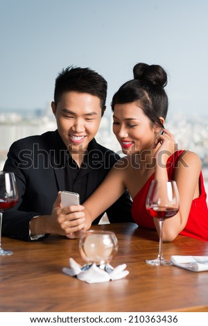 Vietnamese young man showing something on the phone to his girlfriend while sitting in the restaurant - stock photo