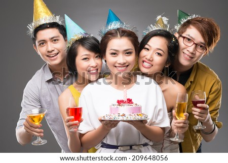 Vietnamese young people with drinks and birthday cake looking at the camera - stock photo