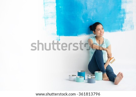 Vietnamese young woman having rest after painting wall in new apartment - stock photo