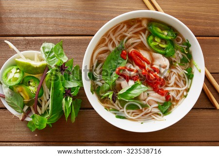 vietnanese beef pho with sriracha sauce shot from overhead view on wooden table - stock photo