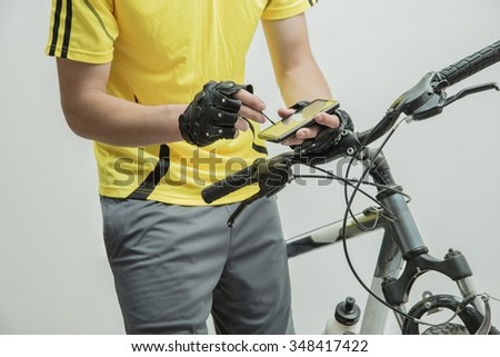 View a map on the mobile phone. Search GPS coordinates Torso man standing near bicycle with navigator looking for something on screen Isolated on white background No face - stock photo