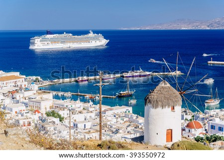 View above Mykonos town with a whitewashed windmill and a cruise ship, Mykonos island, Cyclades, Greece - stock photo