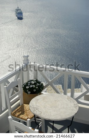 View across a balcony with table and chairs, looking down over the caldera in Santorini, where a cruise ship has arrived - stock photo