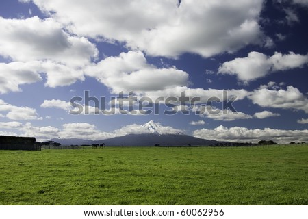 View across a field to a volcano in the distance. - stock photo