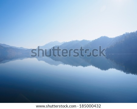 View across Begnas Tal to distant hazy blue hills, Nepal - stock photo