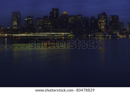 View across Boston Harbor with lights from water taxi and other boats streaked across foreground. Horizontal shot.