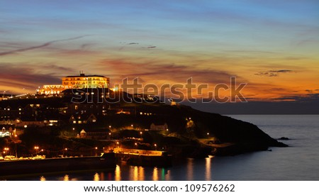 View across Newquay Harbour in Cornwall, England at sunset to the headland beyond. - stock photo