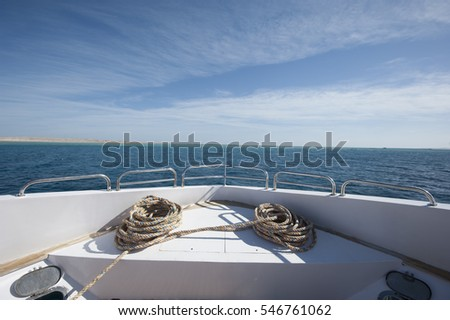View across ocean from bow of a large private motor yacht under way sailing out on tropical sea