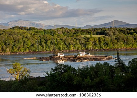 View Across the Menai Straits from Anglesey North Wales UK with a fish farm island - stock photo