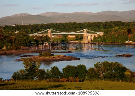 View Across the Menai Straits from Anglesey North Wales UK with the Thomas Telford Suspension Bridge - stock photo