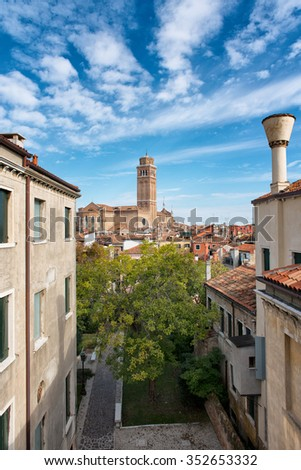View across the rooftops of Venice, Italy of Basilica dei Frari on the skyline under a sunny blue sky with a traditional Venetian chimney in the foreground