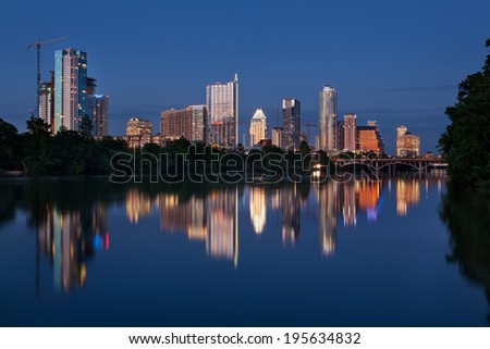 View across Town Lake of downtown Austin with many cranes during building construction.