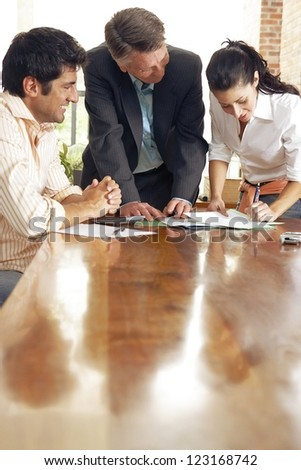 View along a reflectove wooden table top of a young woman signing a contract watched by her smiling husband and the agent - stock photo