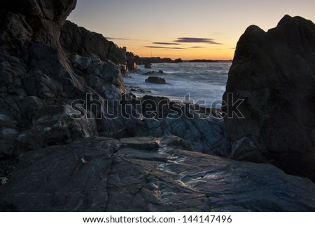 View along a rocky New England beach at sunrise - stock photo