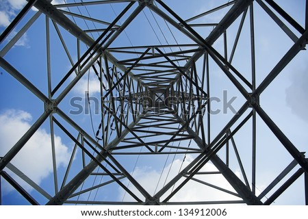 View at a high-voltage electricity pylon from directly below, which deconstructs the subject from its function and treats it as a mere sofisticated geometric abstract. - stock photo