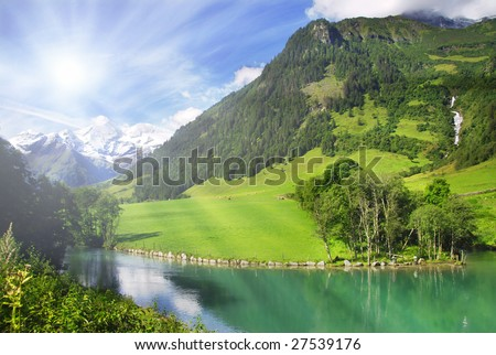 View at alpine mountain peaks from the mountain lake with a sun shining and rays - stock photo