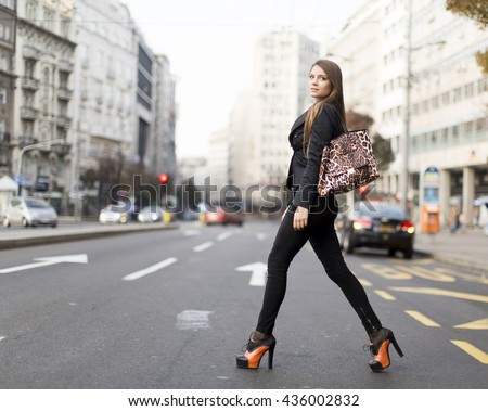 View at attractive young woman walking on a street