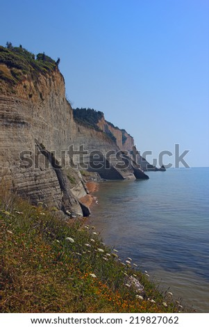 View at beautiful cliffs in Corfu island with flowers on the foreground - stock photo