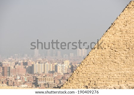 View at the city of Giza in Egypt seen from the Giza Necropolis with part of the pyramid visible. - stock photo