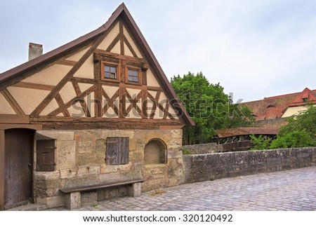View at the city wall with little wooden guard's walkway (round path) of the medieval city of Rothenburg ob der Tauber, Middle Franconia. Seen is an historical gothic building. - stock photo