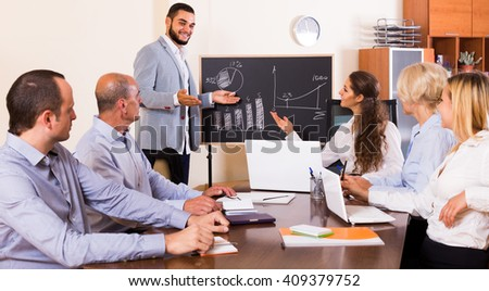 View at working meeting people with diagram at background - stock photo